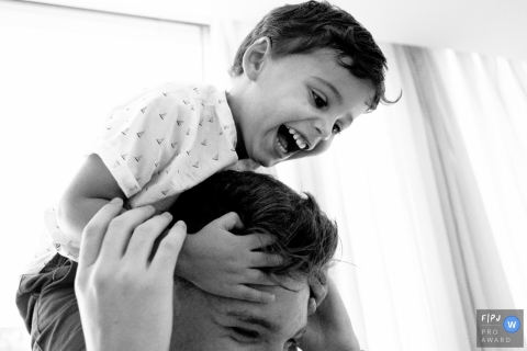 A little boy holds onto his father's head as he rides on his shoulders in this Family Photojournalist Association awarded photo by a Santa Catarina documentary family photographer.