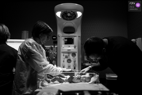 A nurse checks a newborn's heartbeat in the hospital as the father visits in this black and white photo created by an Atlanta, GA birth photographer.