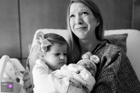 A mother tears up as she and her young daughter hold her newborn infant in the hospital bed in this black and white photo composed by an Atlanta, Georgia documentary birth photographer.