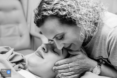 A woman embraces a mother who has just given birth in the hospital in this black and white picture captured by an award-winning Rio de Janeiro, Brazil birth photographer.