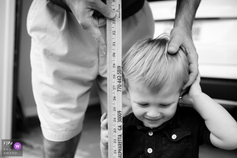 Atlanta, Georgia family session photo of a toddler getting height measured with a yardstick by dad.