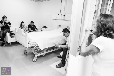 A family waits in a hospital room as one woman prays in this black and white image recorded by a Rio de Janeiro, Brazil birth photographer.