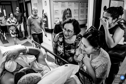 La famille d'une femme l'entoure à l'hôpital pour rencontrer son nouveau-né sur cette photo en noir et blanc prise par un photographe de naissance du Rio Grande do Sul, au Brésil.