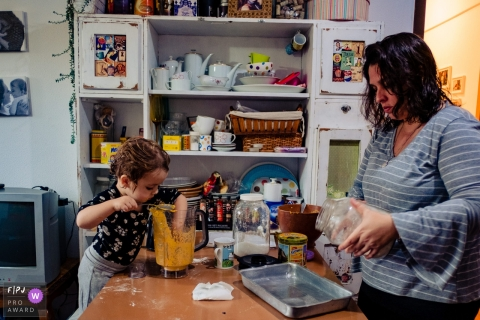 A little girl reaches her hand into a mixture while her mother reads a jar label in this award-winning photo by a Rio Grande do Sul, Brazil family photographer.