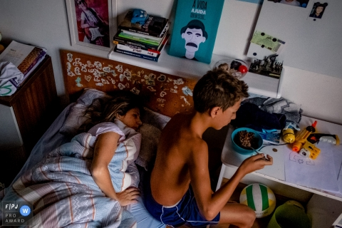 A boy eats cereal as his mom lays in his bed in this photograph created by a Rio Grande do Sul, Brazil family photojournalist.