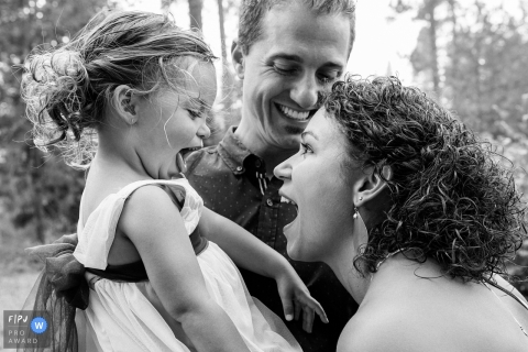 A mother and father smile as they hold their young daughter in this documentary-style family image recorded by a Seattle, WA photographer.