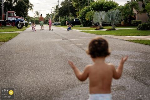 A family rides bikes and scooters down a street while a diaper clad toddler follows behind in this photo captured by a Key West vacation photographer