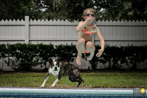 Key West family photojournalist captured this image of a child jumping into a pool while her dog follows suit