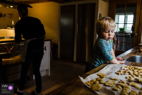 A little boy looks longingly at cookies cooling on the counter in this documentary-style family photo captured by a Copenhagen photographer.