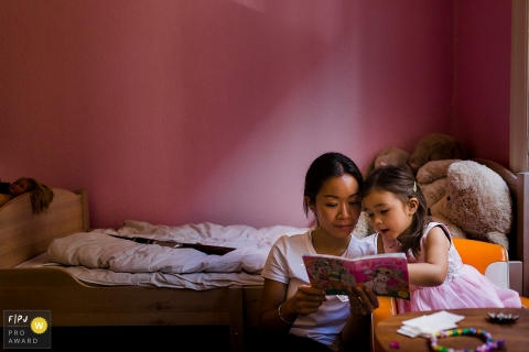 Copenhagen family photojournalist captured this image of a mom and child enjoying a story in a pink walled bedroom