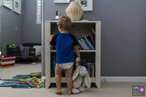 A little boy looks through a bookshelf while holding his stuffed rabbit in this picture captured by a Los Angeles, CA family photojournalist.