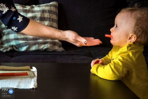 A woman's hand is held out expectantly for the marker cap in her toddlers mouth in this photo captured by a North Rhine-Westphalia documentary family photographer