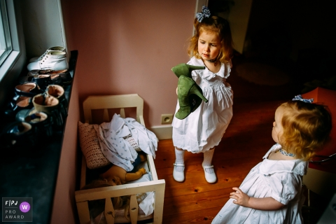 Wallonie documentary family photographer captured this photo of two girls in white dresses inspecting a pair of green high heels