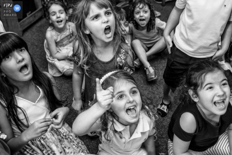 Brazil documentary family photographer captured this black and white photo of a group of children cheering passionately
