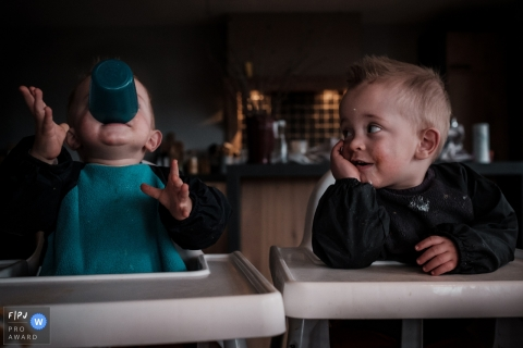 Netherlands documentary family photographer captured this photo of a toddler playing with his empty cup while his food covered twin brother watches in amusement