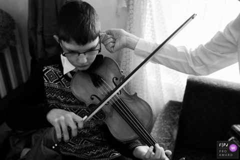 This black and white photo of a boy practicing the violin was captured by a Slovenia documentary family photographer