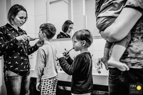 This black and white photo of a family brushing their teeth was captured by a Netherlands documentary family photographer