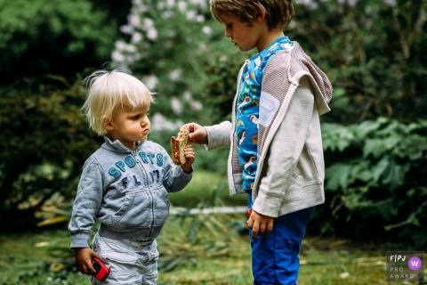 Wallonie documentary family photographer captured this photo of two brothers sharing a sandwich in the yard