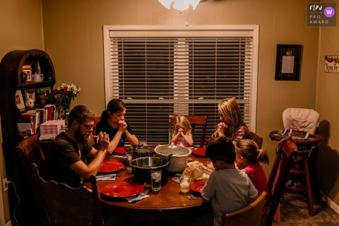 San Francisco documentary family photographer captured this photo of a family saying grace before eating their family meal