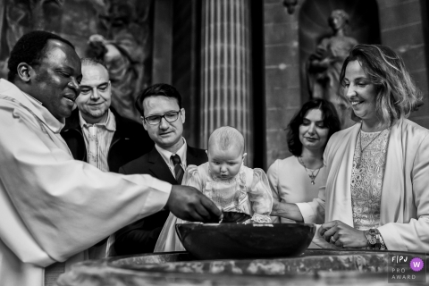 France documentary family photographer captured this black and white photo of a baby's baptism with a priest inside a church.