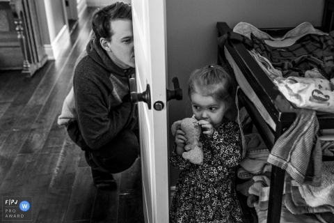 This black and white photo of a young girl playing hide and seek with her father was captured by an Ontario documentary style family photographer