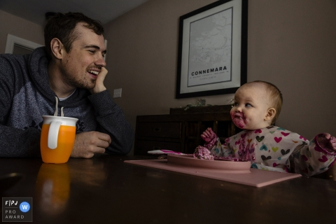 A very messy toddler gives a playful look to her father as she feeds herself at the table in this photo captured by an Ontario documentary family photographer