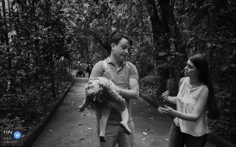Para documentary family photographer captured this black and white photo of a father carrying a tired toddler out of the park as her mother walks nearby
