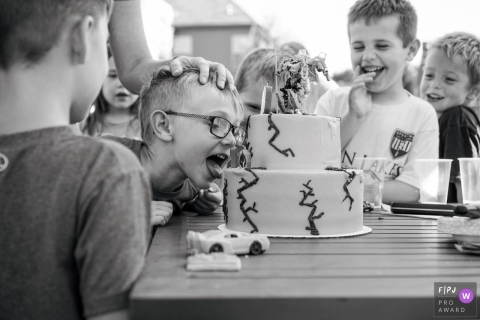 Kansas City documentary style family photographer captured this photo of a young boy licking his birthday cake surrounded by his laughing friends