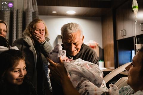 Le photographe de famille documentaire de Pittsburgh saisit cette photo de fiers grands-parents qui rencontrent le petit-enfant pour la première fois lors d'une naissance à l'hôpital