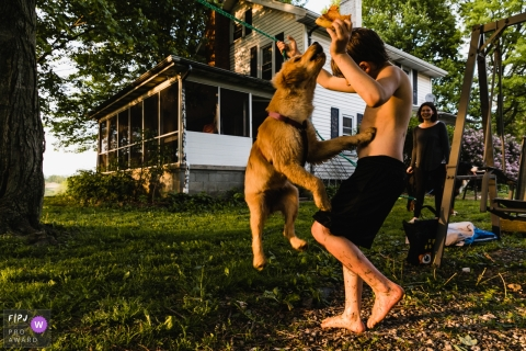 Pittsburgh documentary family photographer captured this photo of a dog trying to steal his young owners pizza while playing in the yard