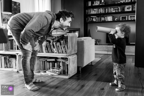 A little boy looks at his father through a cardboard tube in this FPJA award-winning picture by a Modena family photographer.