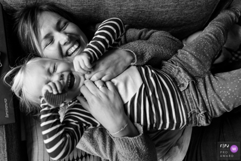 A mother holds her daughter as they lay on the couch and laugh in this photograph by a Modena documentary family photographer.