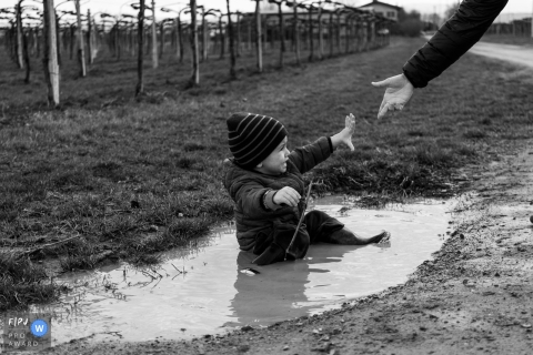A mother reaches down to help her little boy up after he fell in a puddle in this Family Photojournalist Association awarded photo by a Modena documentary family photographer.