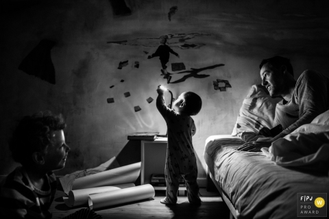A little boy plays with a lamp while his father and brother watch in this photo by an Antwerpen award-winning family photographer.