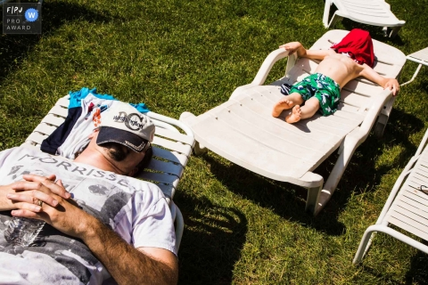 A father and son lay on lawn chairs with their faces covered in this Family Photojournalist Association contest awarded photo created by a Pittsburgh family photographer.