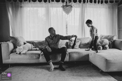 A boy stands on a couch as his father takes off his socks in this documentary-style family photo captured by a Pistoia photographer.