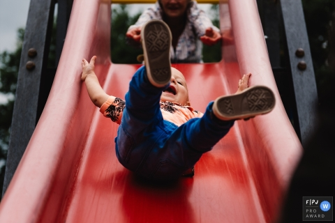 A little boy laughs as he goes down a playground slide in this Family Photojournalist Association awarded photo by a Gelderland, Netherlands documentary family photographer.