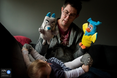 A father plays with two puppets while his baby boy watches in this photo recorded by an Amsterdam award-winning, documentary-style family photographer.