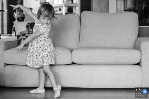 A little girl practices ballet in the living room in this image created by a Berlin, Germany family photographer.