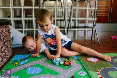 Two brothers play with toy cars on the floor in this photo recorded by an Aveiro, Portugal award-winning, documentary-style family photographer.