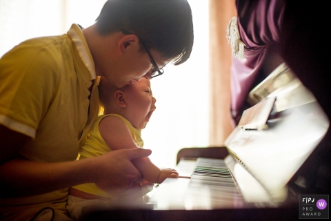 A father helps his baby play the piano in this photograph created by a Hangzhou City family photojournalist.