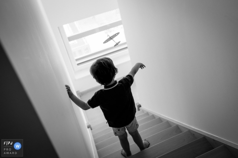 A little boy flies a toy airplane down the stairs in this documentary-style family image recorded by a Nantes photographer.