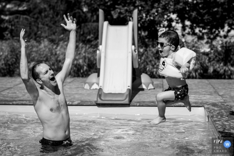 A father cheers as his little boy jumps into the pool in this FPJA award-winning picture by a Nantes family photographer.