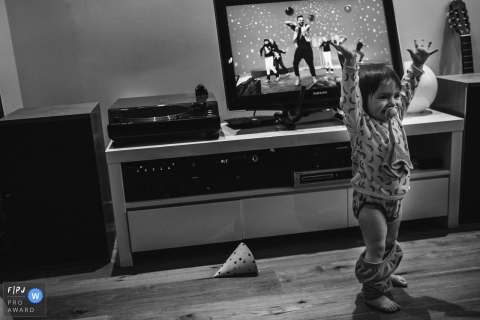 A little girl excitedly throws her hands up in the air as her pants accidentally fall down in this Family Photojournalist Association awarded photo by an Antwerpen documentary family photographer.