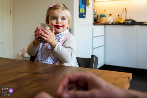 A little girl looks up with grape juice on her face after taking a sip from her cup in this image created by a Netherlands family photographer.