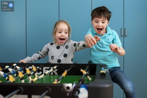 Un frère et une sœur jouent ensemble au baby-foot avec enthousiasme dans cette photo prise par un photojournaliste de famille néerlandais.