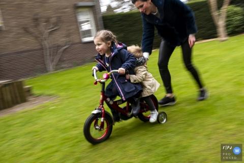 Une mère aide ses deux jeunes filles à faire du vélo sur cette photo d'un photographe de famille néerlandais primé.