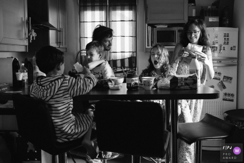 A family eats breakfast together sleepily in the morning in this photograph created by a Paris, France family photojournalist.