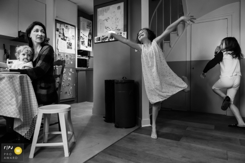 Two little girls dance around while their mother watches in this documentary-style family image recorded by a Paris, France photographer.