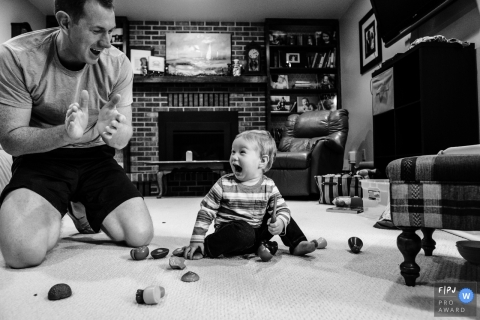 A baby boy laughs as his father claps in this photo by a Boulder, CO award-winning family photographer.